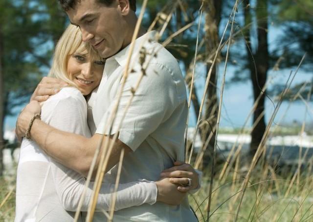Glückliche Serbin mit glücklichem deutschen Mann, der sie umarmt